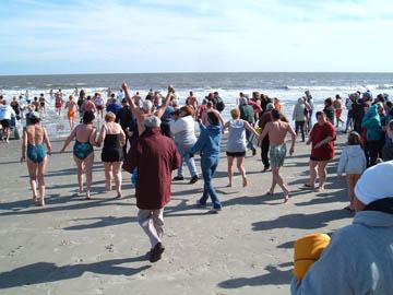 members run into the ocean